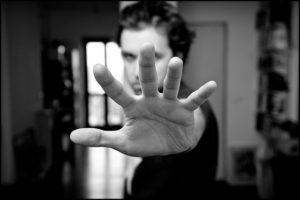 Na obrazku mężczyzna wyciąga rękę by zatrzymać jakąś sytuację. Zdjęcie jest czarno-białe.