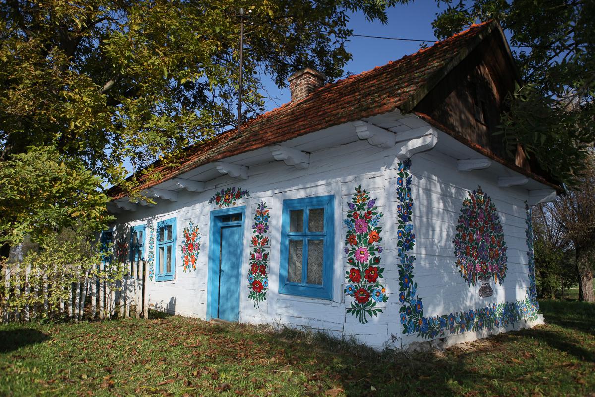 na zdjęciu drewaniana chata pomalowana w kwiaty