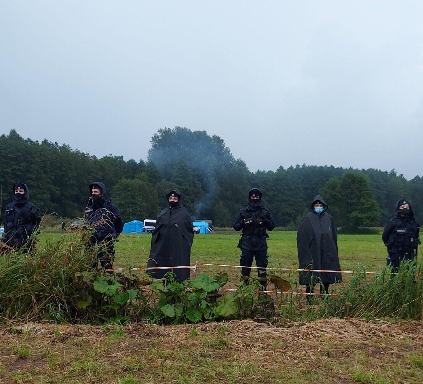 na zdjęciu policjanci w stoją szpalerem wzdłuż prowizorycznego ogrodzenia z białopczerwonej wstążki