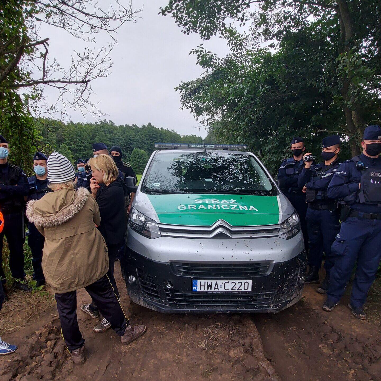 na zdjęciu na błotnistej drodze stoi samochód straży granicznej. Wokół niego zgromadzeni są strażnicy, policjanci i działacze organizacji społecznych